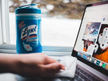 Person Cleaning Laptop with lysol