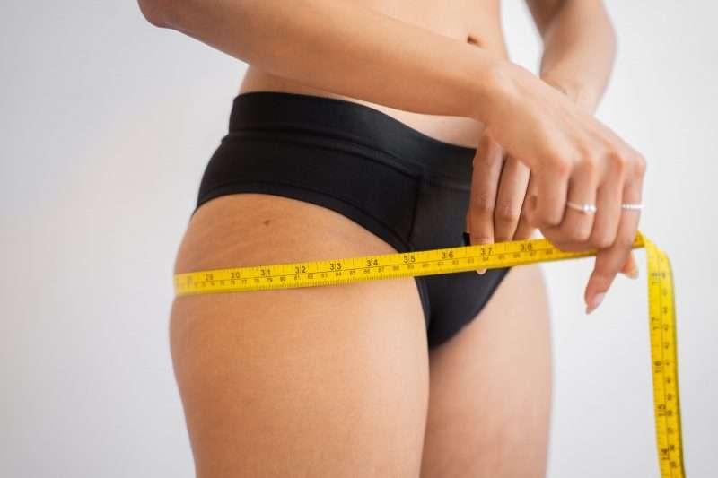 woman measuring leg weight loss diet