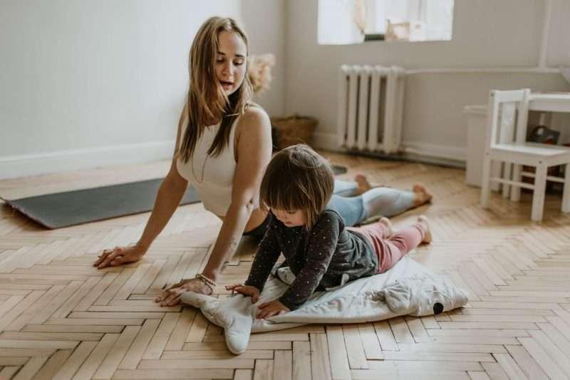 woman and kid doing yoga